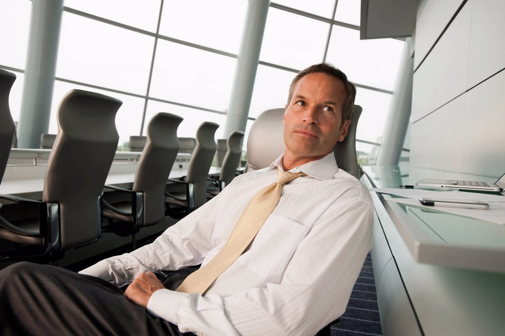 Serious Caucasian businessman sitting in conference room : Stock Photo