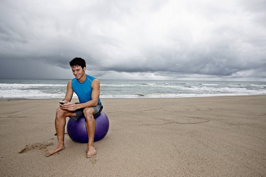 Young man sitting beach text messaging on cell phone : Stock Photo