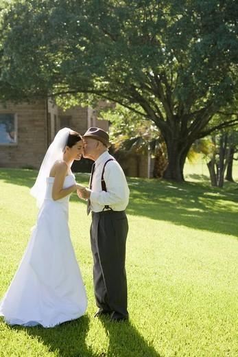 Hispanic grandfather giving bride a kiss : Stock Photo