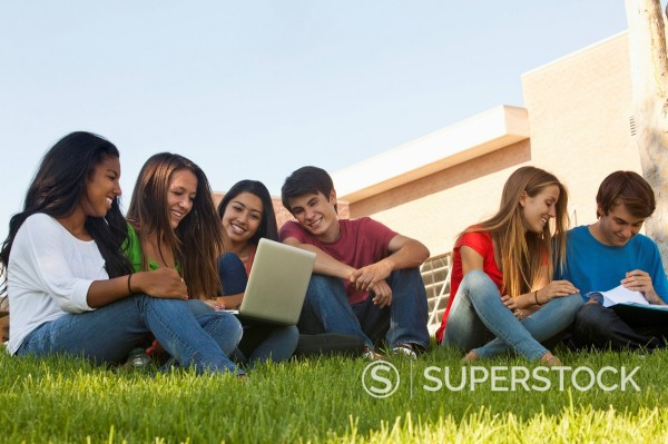 Friends sitting in grass doing homework : Stock Photo