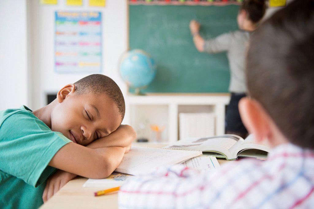 African American boy sleeping in classroom : Stock Photo