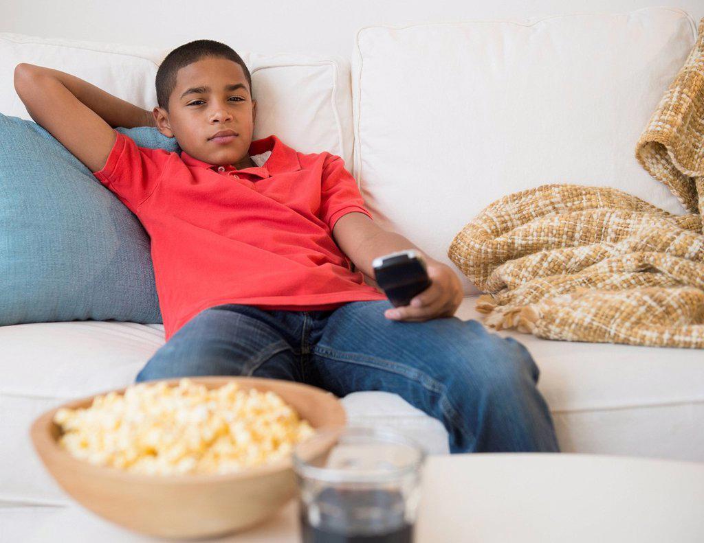 Hispanic boy watching television : Stock Photo