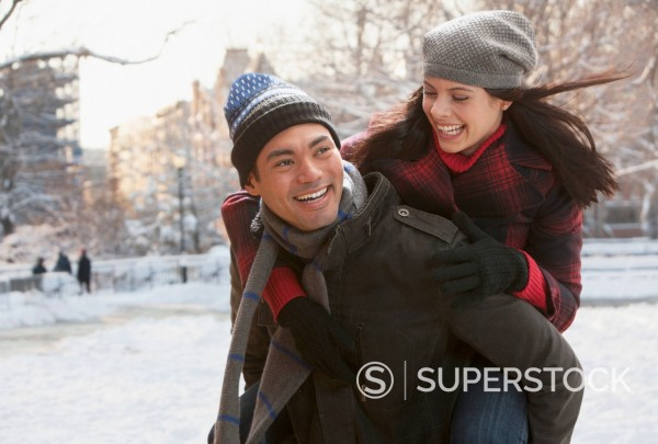 Mixed race man carrying girlfriend on back : Stock Photo