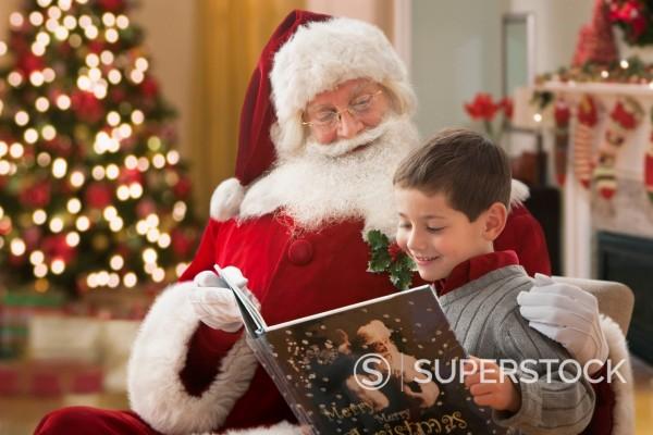 Stock Photo: 1589R-166925 Santa reading book to Caucasian boy