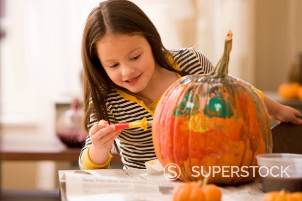 Caucasian girl decorating pumpkin : Stock Photo