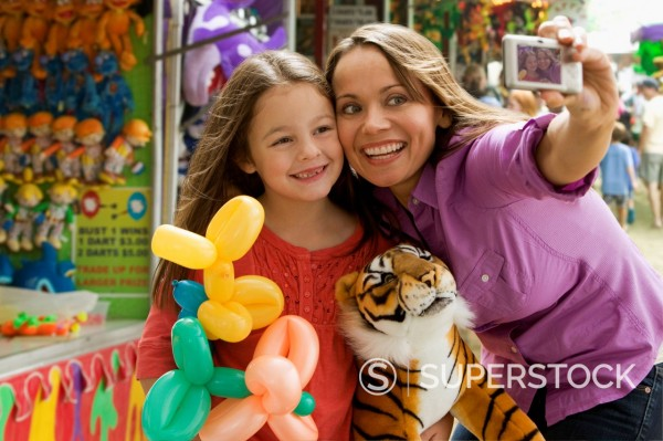 Caucasian mother and daughter taking self_portrait at fair : Stock Photo