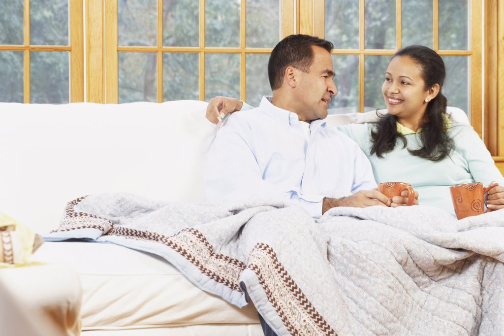 Stock Photo: 1589R-16723 Couple sitting on the couch under a blanket together