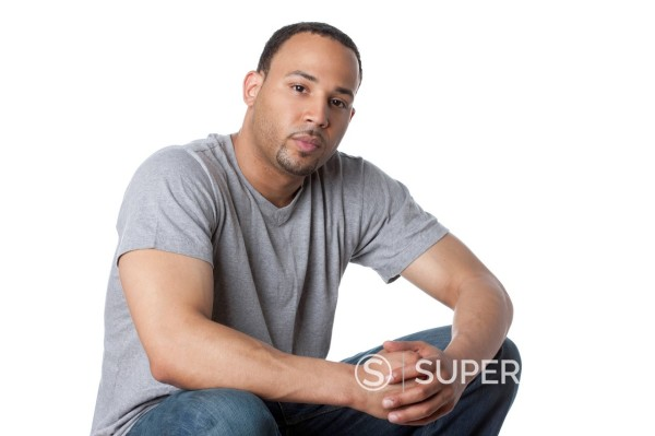 Serious mixed race man with hands clasped : Stock Photo