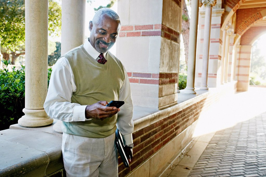 Stock Photo: 1589R-167716 Black professor text messaging on cell phone