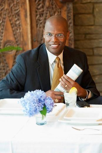 Black businessman holding newspaper in restaurant : Stock Photo