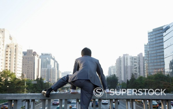 Chinese businessman climbing over urban railing : Stock Photo