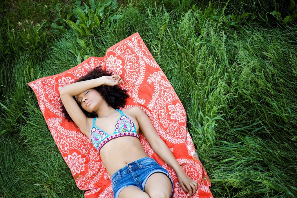 Stock Photo: 1589R-168425 Hispanic woman laying in grass taking nap