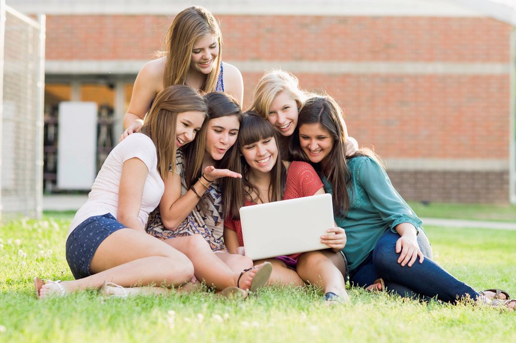 Caucasian friends looking at laptop together : Stock Photo