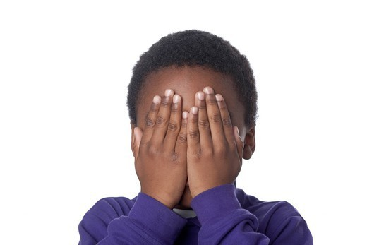Mixed race boy covering face : Stock Photo