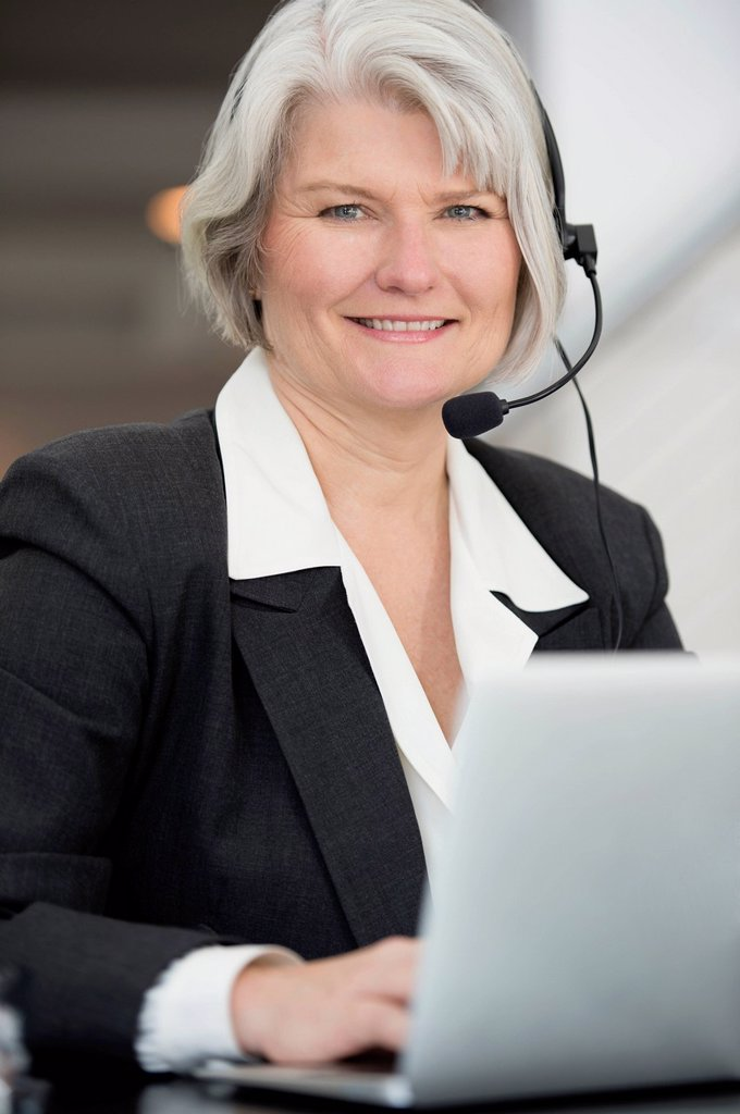 Stock Photo: 1589R-168675 Smiling Businesswoman in headset typing on laptop