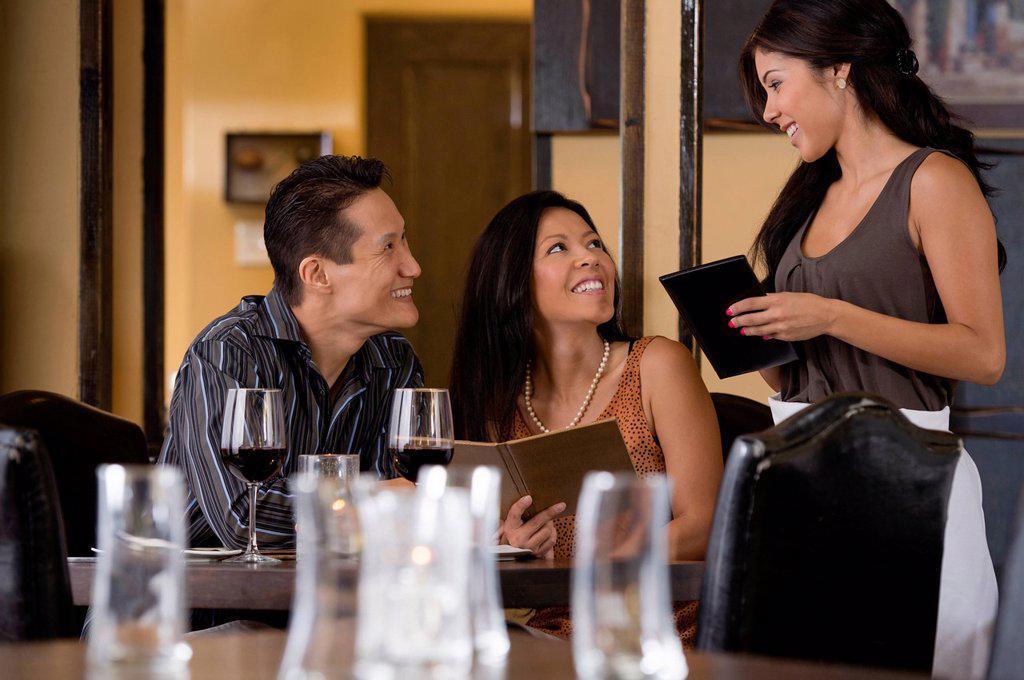 Waitress taking couple´s order in restaurant : Stock Photo