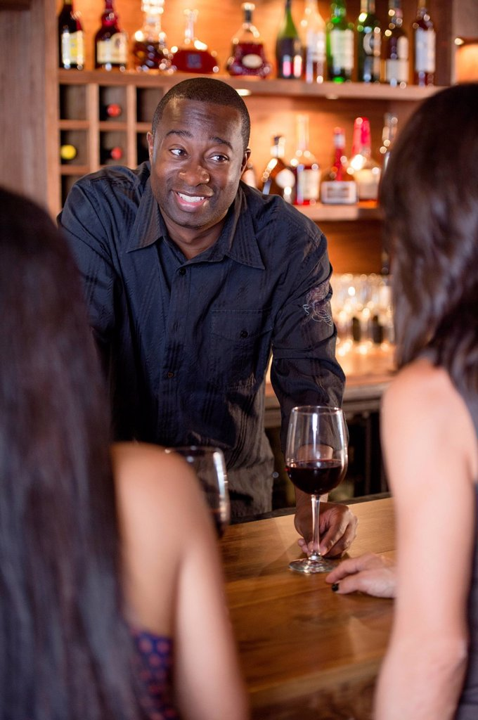 Stock Photo: 1589R-168699 African American bartender serving customers