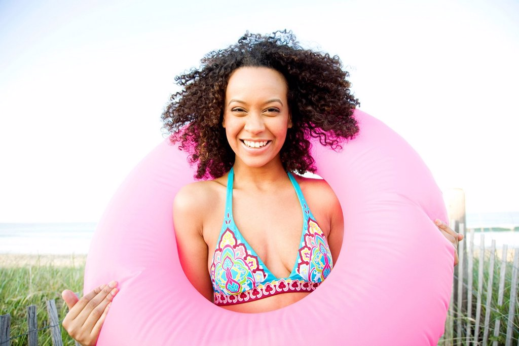 Stock Photo: 1589R-168776 Smiling Hispanic woman holding inflatable ring