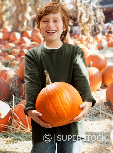 Caucasian boy holding pumpkin : Stock Photo