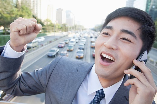 Chinese businessman on overpass talking on cell phone : Stock Photo