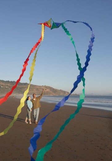 Couple flying kite at beach : Stock Photo