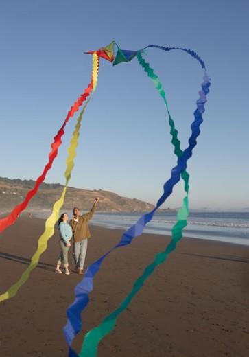Stock Photo: 1589R-16911 Couple flying kite at beach