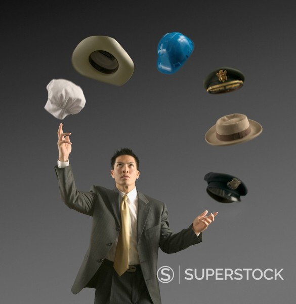 Young businessman juggling six hats : Stock Photo