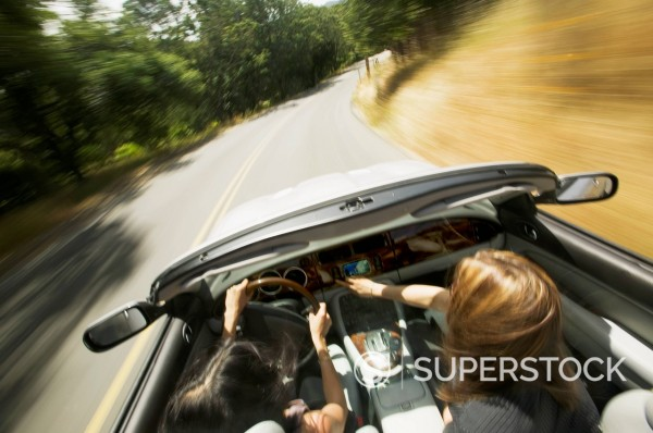 Young women driving in convertible : Stock Photo