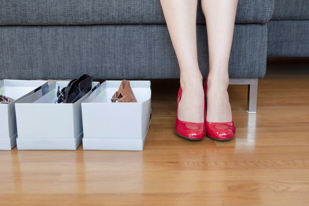 Stock Photo: 1589R-169507 Woman´s feet with shoe boxes on floor