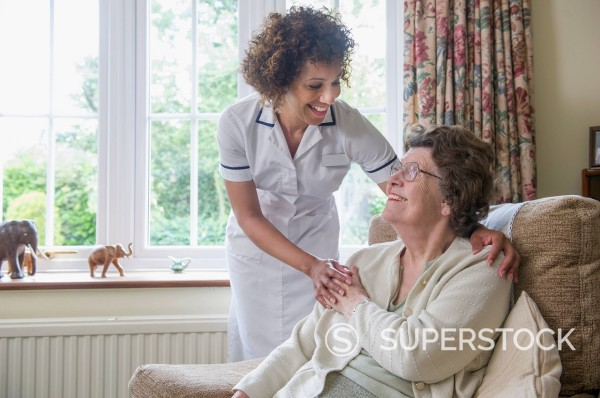 Stock Photo: 1589R-169526 Older woman talking to caretaker in home