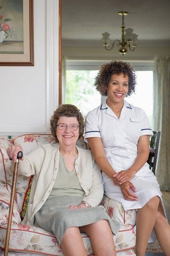 Older woman sitting with caretaker in home : Stock Photo