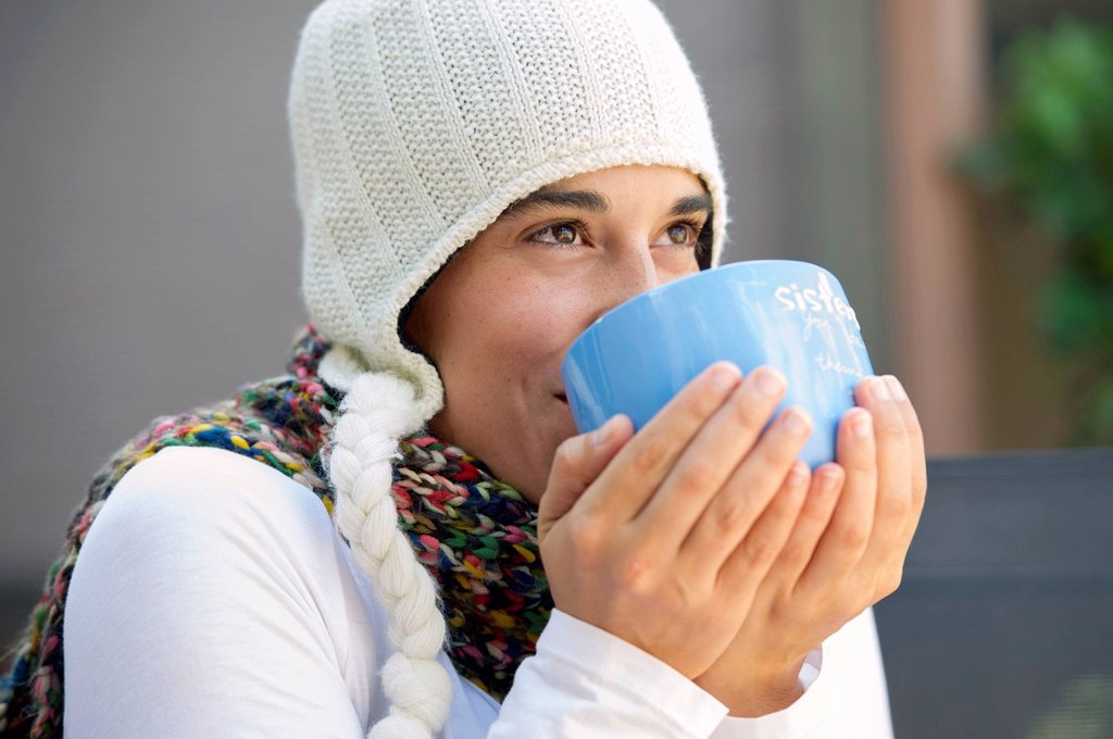 Stock Photo: 1589R-169594 Hispanic woman drinking coffee outdoors