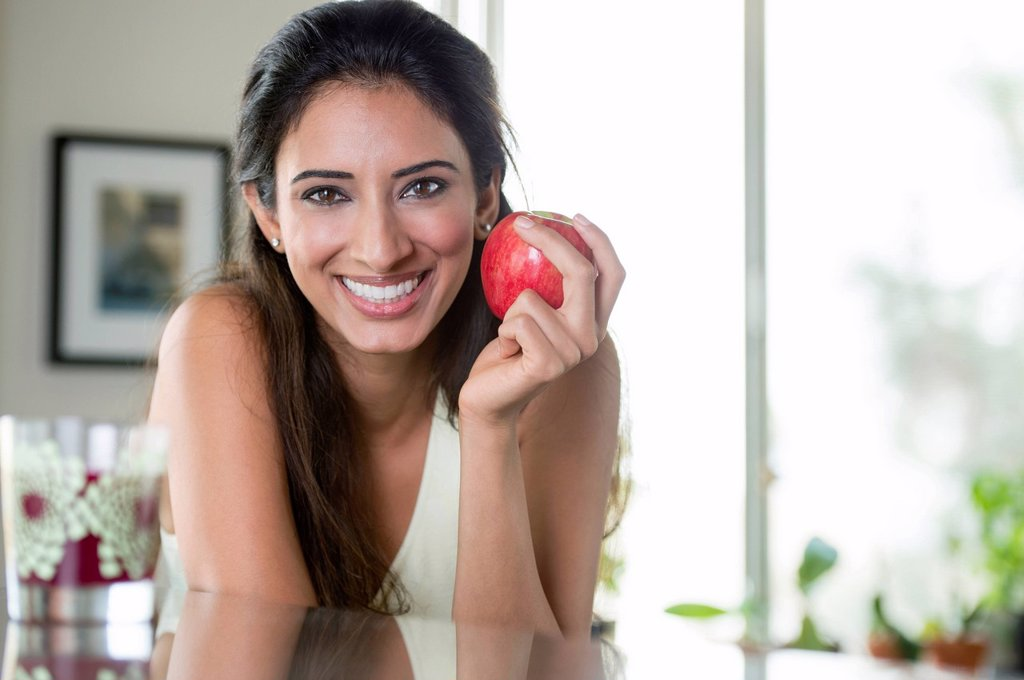Indian woman holding apple in kitchen : Stock Photo