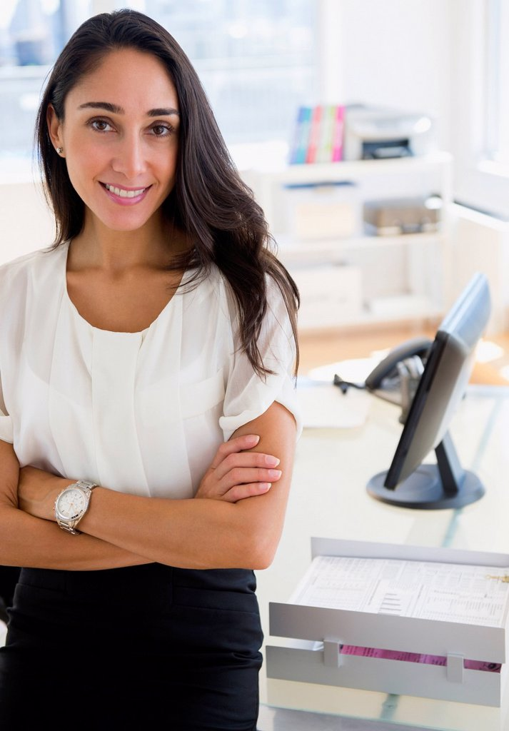 Caucasian businesswoman standing at desk : Stock Photo