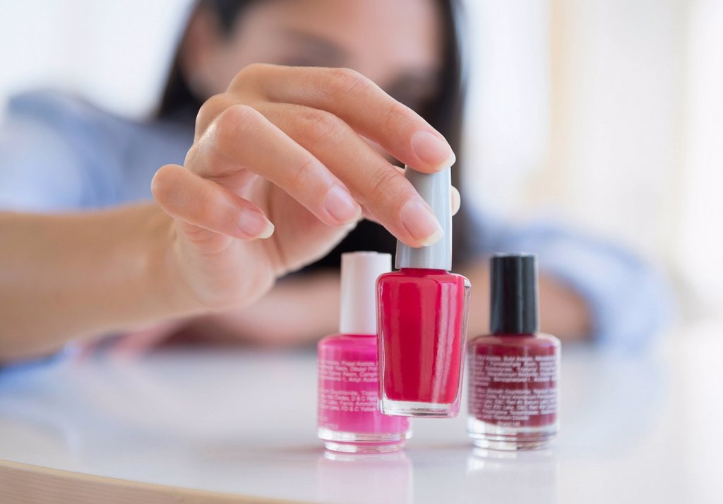 Stock Photo: 1589R-169647 Caucasian woman selecting bottle of nail polish