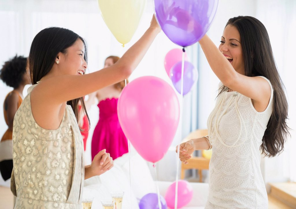 Stock Photo: 1589R-169706 Women playing with balloons at party