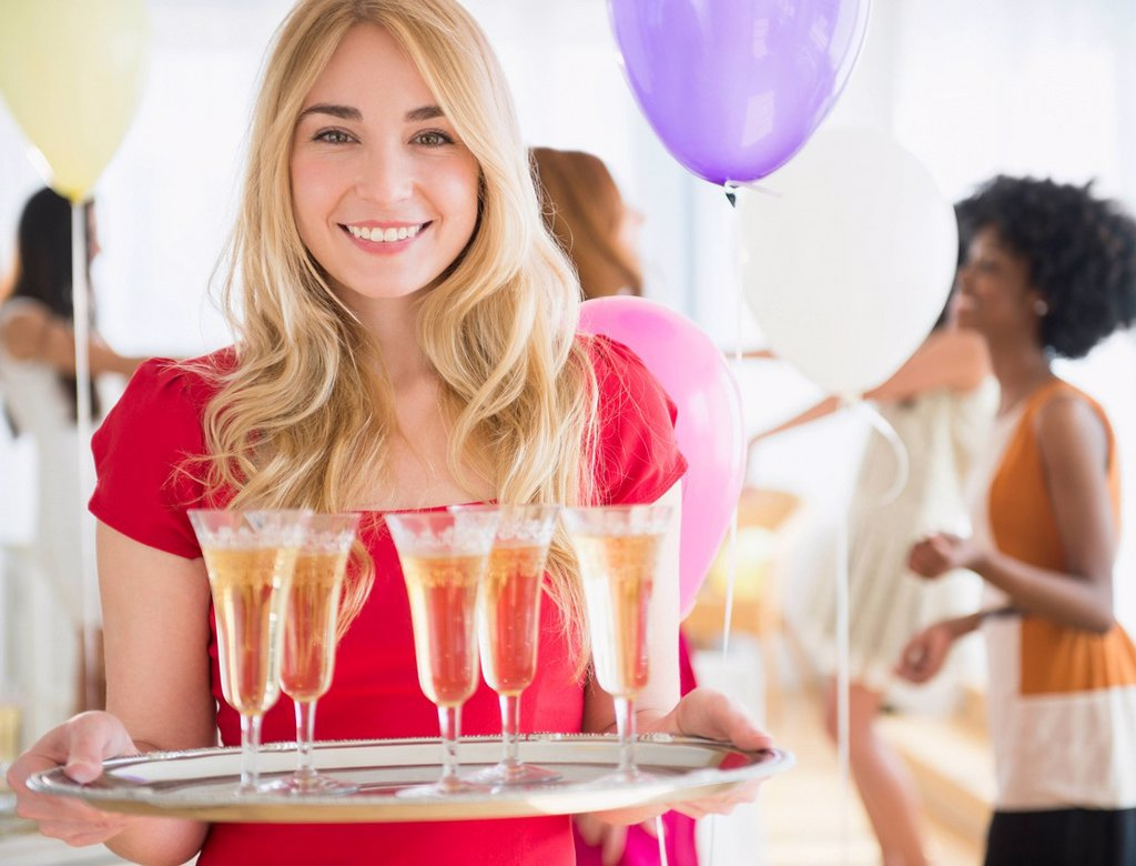 Stock Photo: 1589R-169710 Smiling woman carrying tray of champagne
