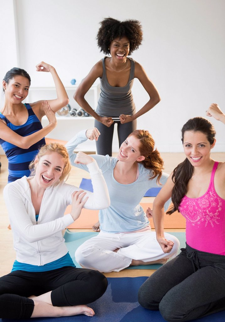 Stock Photo: 1589R-169734 Women showing muscles on yoga mats