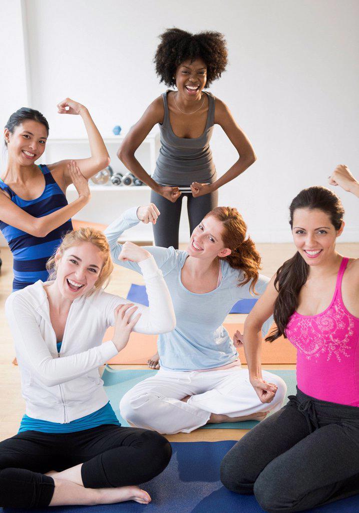 Women showing muscles on yoga mats : Stock Photo