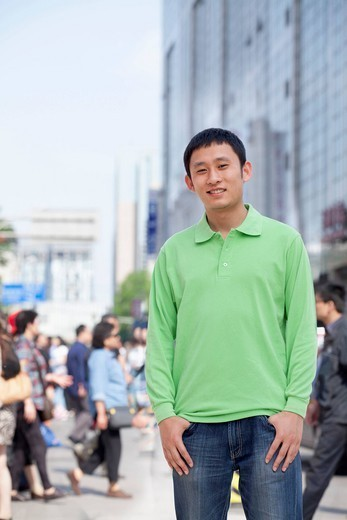 Smiling man standing on city street : Stock Photo
