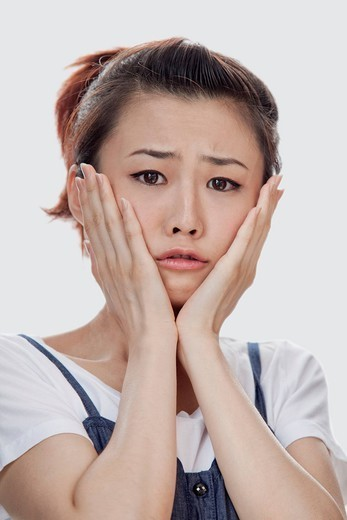 Sad Asian woman with head in hands : Stock Photo