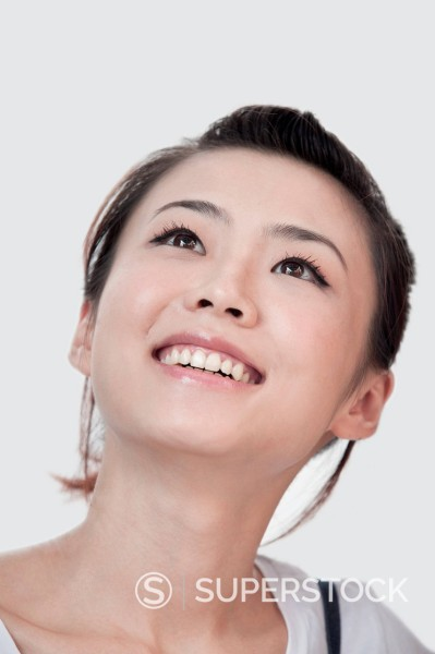 Smiling Asian woman looking up : Stock Photo