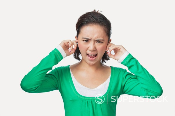 Chinese woman with fingers in ears : Stock Photo