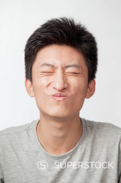 Stock Photo: 1589R-169871 Chinese man making puckering expression