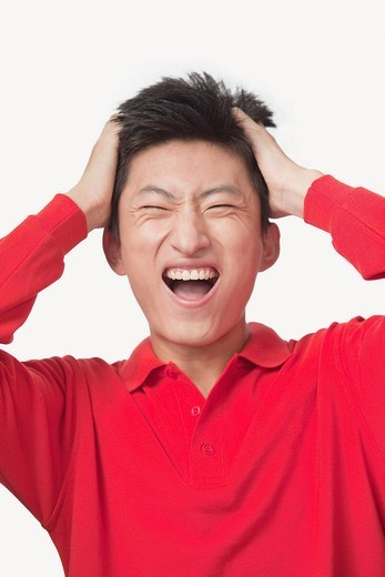 Frustrated Chinese man with head in hands : Stock Photo