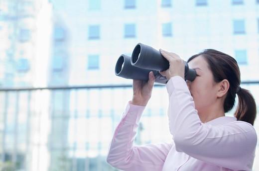 Chinese businesswoman using binoculars : Stock Photo