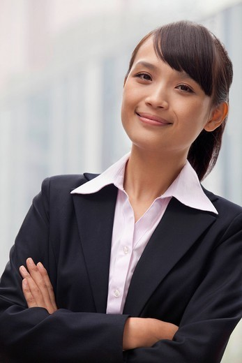 Smiling Chinese businesswoman with arms crossed : Stock Photo