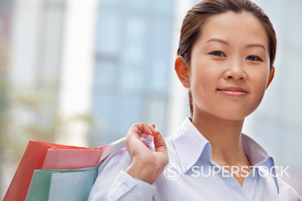 Stock Photo: 1589R-169965 Chinese businesswoman carrying shopping bags