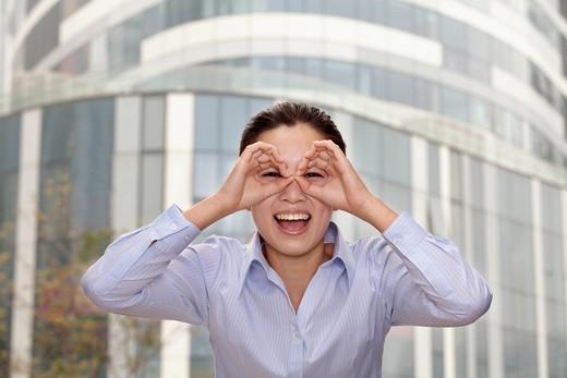 Chinese businesswoman peering through hands : Stock Photo