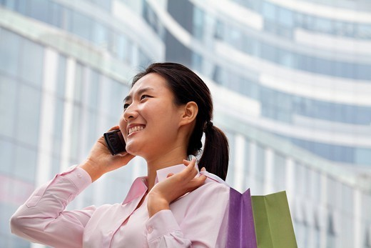 Chinese businesswoman talking on cell phone and carrying shopping bags : Stock Photo